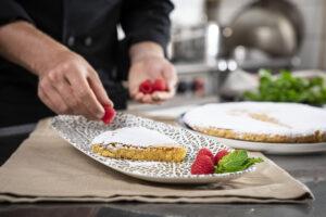 Mano de cocinero decorando a mano una tarta de Santiago con frambuesas