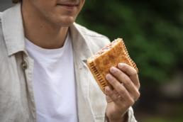 Hombre comiendo empanada