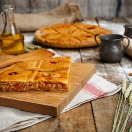 Foto de empanada jugosa con pimientos asomando y accesorios de cocina variados