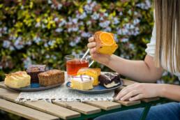 Mujer comiendo pasteles en entorno bucólico