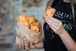 Mujer sacando una mini empanadilla de una bolsa para comerla